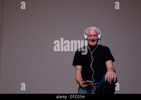 Portrait of senior man listening to MP3 player on headphones - Stock Photo