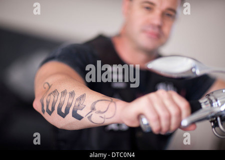 Close up of mature man sitting on motorcycle indoors - Stock Photo