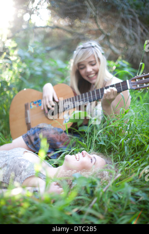 Two teenage girls listening to guitar in woodland - Stock Photo