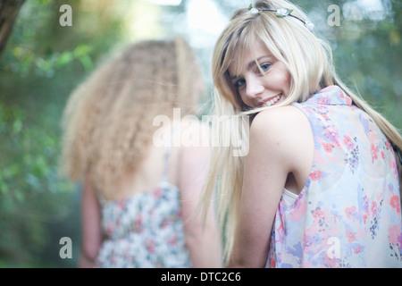 Two teenage girls strolling in woodland - Stock Photo