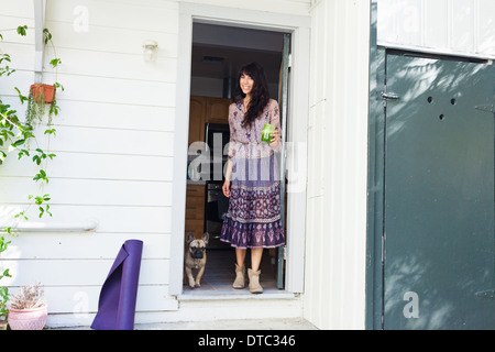 Young woman in doorway with vegetable juice - Stock Photo