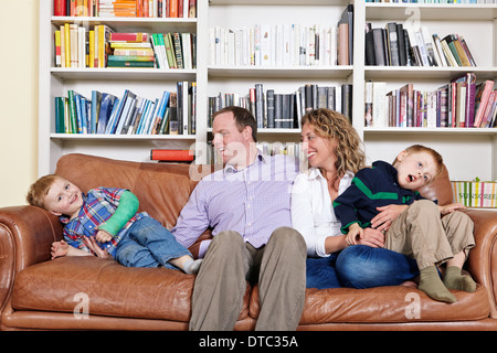 Mid adult parents and young sons having fun on sofa - Stock Photo