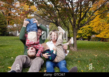 Mid adult parents and young sons playing in garden - Stock Photo