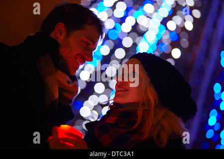 Young couple holding candle in front of city xmas lights - Stock Photo
