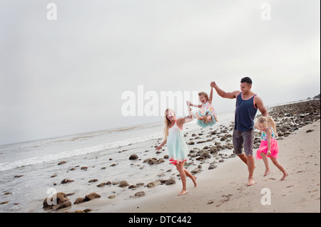 Parents and two young girls walking on beach - Stockfoto