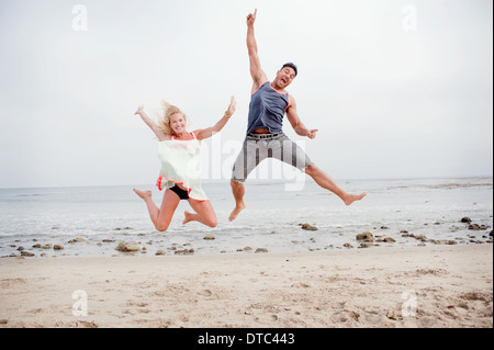 Pregnant couple jumping mid air on the beach - Stockfoto
