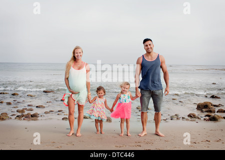 Parents and two young girls strolling on beach - Stockfoto