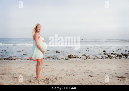 Portrait of pregnant young woman on beach - Stockfoto