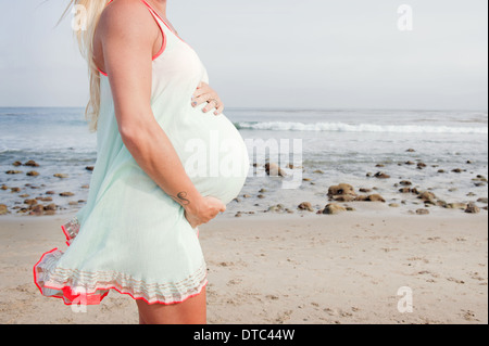 Cropped image of pregnant young woman on beach - Stockfoto