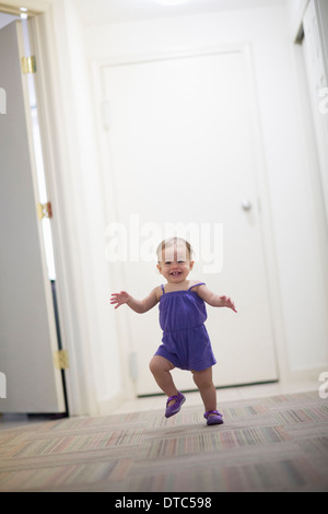 Toddler girl learning to walk - Stock Photo
