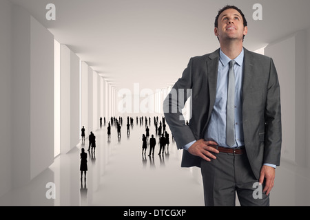 Composite image of smiling businessman with hand on hip - Stock Photo