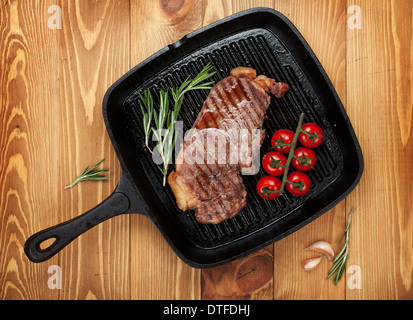 Sirloin steak with rosemary and cherry tomatoes on frying pan over wooden table - Stock Photo