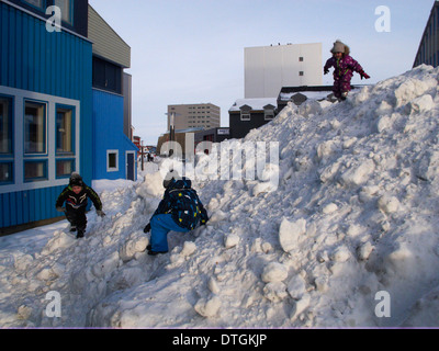 Nuuk center, on the main street, ung boys and girls are playing on a mountain of snow. - Stock Photo