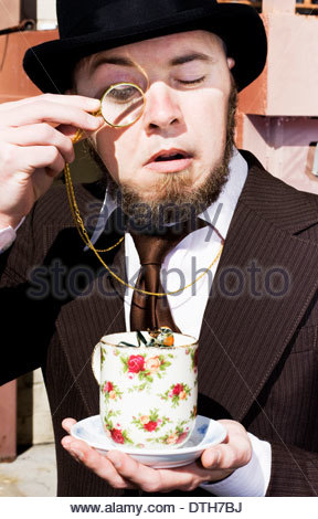 Vintage Man Startled While Looking Thorough A Monicle At A Fly In His Cup Of Tea - Stock Photo