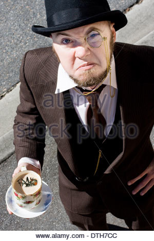 Vintage Gent Stands Looking Bugged By The Fly In His Cup Of Tea - Stock Photo