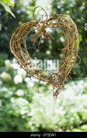A heart shape made out of woven twigs hanging from a tree Simple decorations  England - Stock Photo