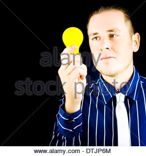 Young business man holding light bulb in hand on black background with copy space - Stock Photo