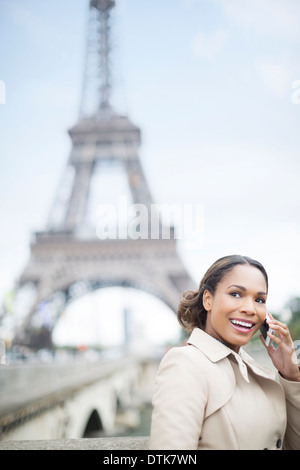 Woman talking on cell phone by Eiffel Tower, Paris, France - Stock Photo