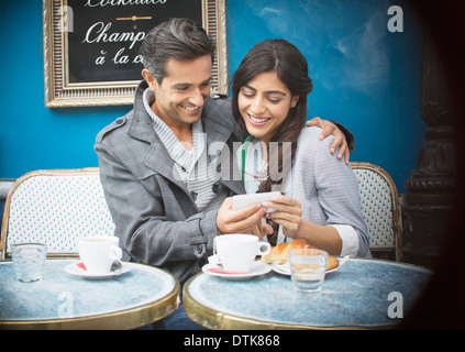Couple using cell phone at sidewalk cafe, Paris, France - Stock Photo