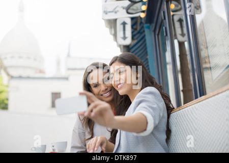 Friends taking self-portrait at sidewalk cafe near Sacre Coeur Basilica, Paris, France - Stock Photo