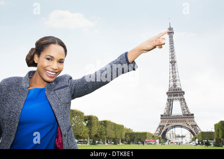 Woman posing as if to touch Eiffel Tower, Paris, France - Stockfoto