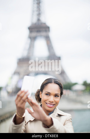 Woman taking self-portrait in front of Eiffel Tower, Paris, France - Stock Photo