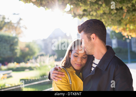 Couple hugging in urban park - Stock Photo