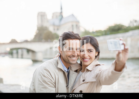 Couple taking self-portrait along Seine River near Notre Dame Cathedral, Paris, France - Stock Photo