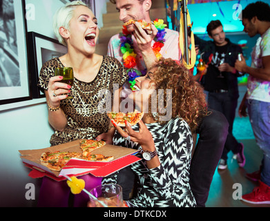 Friends eating pizza at party - Stock Photo