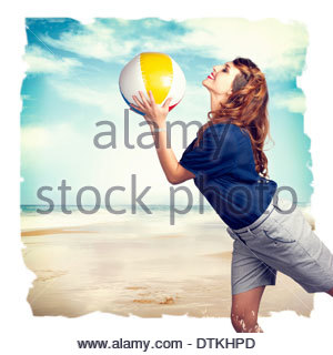 Happy retro woman playing with a beach ball in the sand - Stock Photo