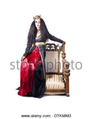 Queen with crown sitting on wooden throne chair, white studio background - Stockfoto