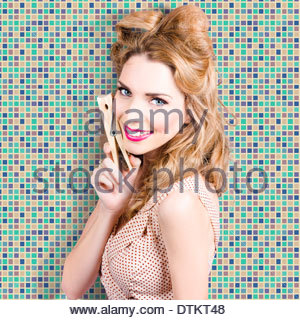 Housework with a smiling young woman holding large peg when partaking in laundry duties - Stock Photo