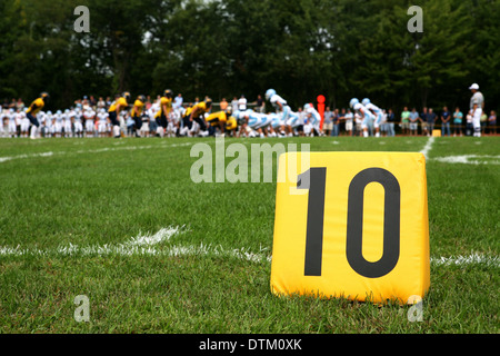 ten yard line marker with football play behind - Stock Photo