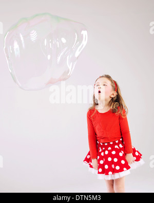 Little cute girl making the soap bubbles - Stock Photo