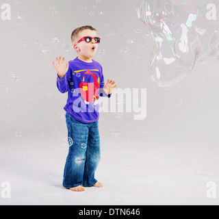 Little child playing with soap bubbles - Stock Photo
