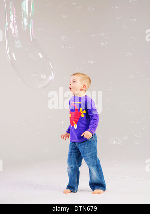 Little cute kid playing a soap bubbles - Stock Photo