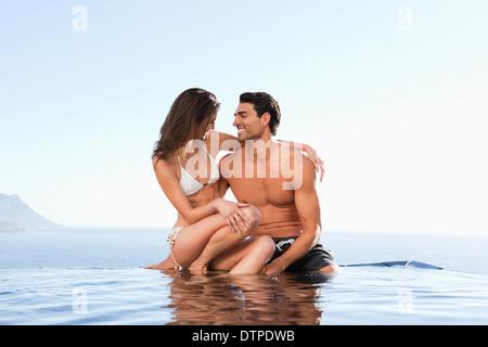 Couple sitting on pool edge together - Stock Photo