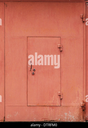 Red metal garage wall with locked door. Background texture - Stock Photo