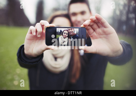 Mixed race young boy and girl making a funny face while taking a self portrait with mobile phone. Cute young couple. - Stock Photo