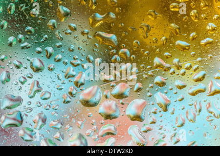 A bright colorful background image of water droplets on a glass surface - Stock Photo