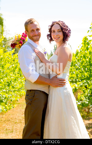 Bride and groom together for a portrait in a vineyard in Oregon on their wedding day. - Stock Photo
