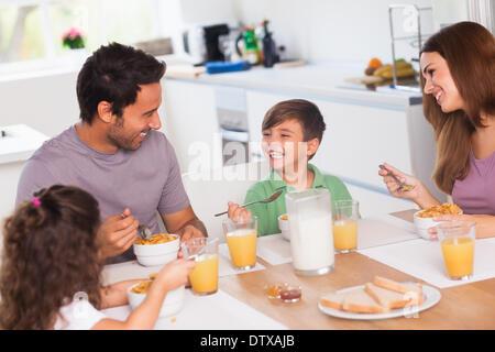 Family laughing around breakfast - Stock Photo