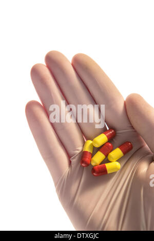 Gloved hand holding tablets in palm - Stock Photo