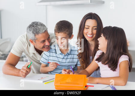 Smiling family drawing together in kitchen - Stock Photo