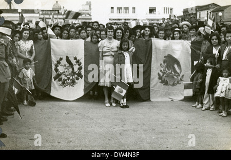 Circa 1940 photograph, group of Hispanic people holding the flags of Guatemala and Mexico. - Stockfoto