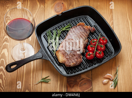 Sirloin steak with rosemary and cherry tomatoes on a frying pan with glass of wine - Stock Photo