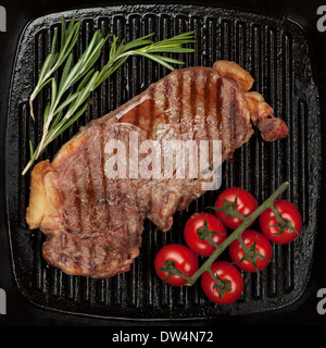 Sirloin steak with rosemary and cherry tomatoes on frying pan closeup - Stock Photo