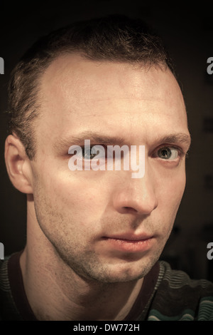 Young serious Caucasian man closeup portrait on dark background - Stock Photo