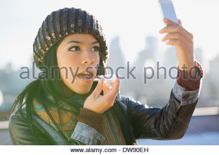 Woman using smart phone to apply lipstick outdoors - Stock Photo
