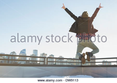 Rear view of woman jumping against cityscape - Stock Photo